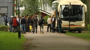 Asielzoekers en een bus foto RTV Noord