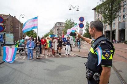 Gay Pride Amsterdam politie met regenboogvlag